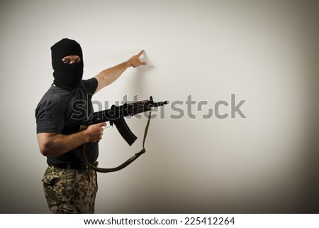 Man with gun is showing something on the wall.