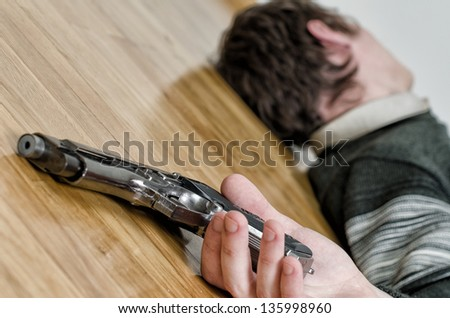 Man with gun laying on the floor