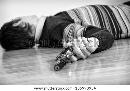 Man with gun laying on the floor. Black and white - stock photo