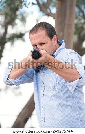 man with gun pointing to camera - stock photo