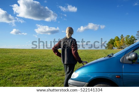 Man with hair tied into a ponytail watching the white clouds in the blue sky beside blue car parked on a greenfield site.