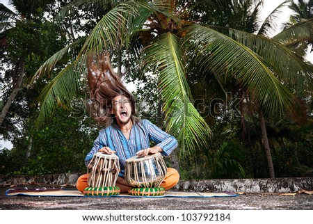 Man with hair up playing on traditional Indian tabla drums at palm trees background - stock photo