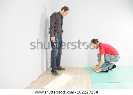 Man with hammer looking at  flooring installation - stock photo