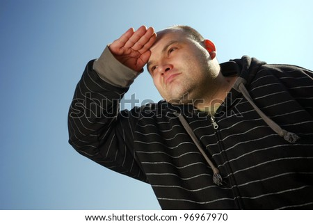 man with hand on forehead in front of blue sky - stock photo