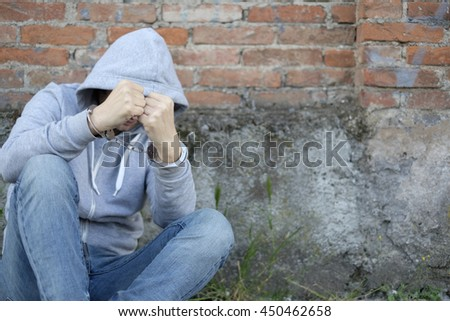 Man with handcuffs arrested in the street - stock photo