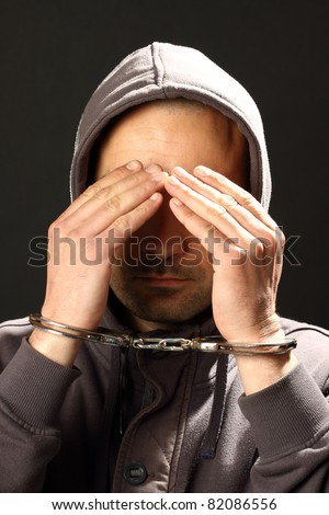 man with handcuffs, hiding his face