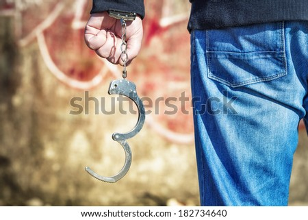 Man with handcuffs near the old wall - stock photo