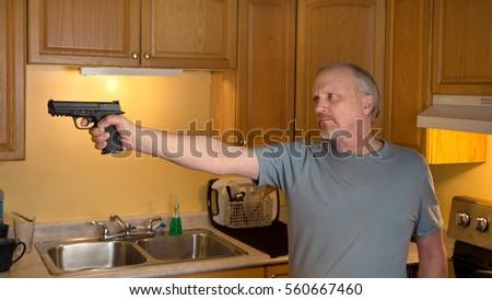 Man With Handgun In Kitchen, Gun In Focus Only, Trigger Finger In The  Register