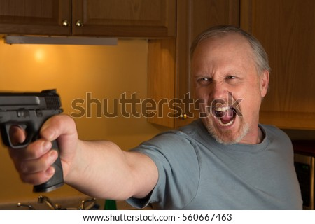Charming Man With Handgun In Kitchen, Gun In Focus Only, Trigger Finger In The  Register