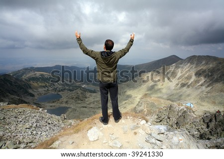 man with hands in the air standing at edge of a rock viewing the landscape