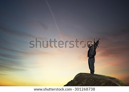 man with hands raised in the sunset concept for religion, worship, prayer and praise - stock photo