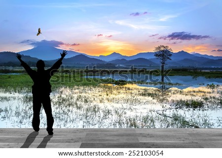 Man with hands raised to beautiful sunset - stock photo