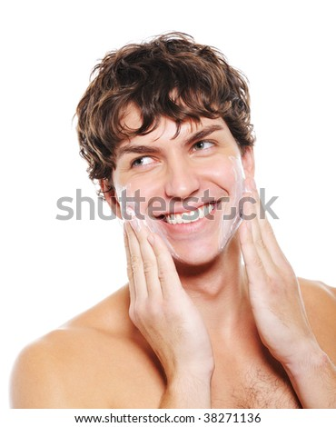Man with happy smile applying moisturizing lotion after shaving for his face - stock photo