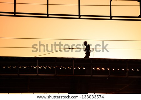 man with hard hat working on the roof near sunset - stock photo