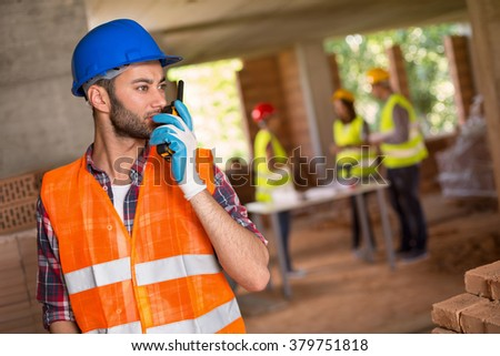 Man with hardhat and walky talky radio at construction site - stock photo