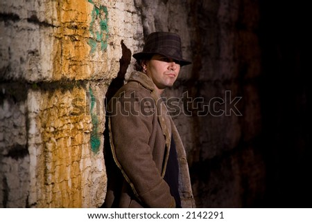 Man with hat and coat in dark alley - stock photo