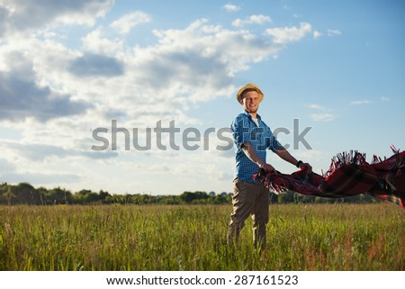 man with hat in sunny day in the park with picnic blanket