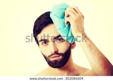 Man with headache and ice bag on his head. - stock photo