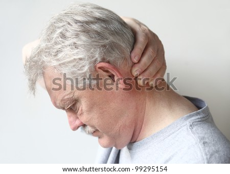 man with headache at base of skull - stock photo