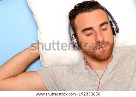 man with headphones in bed - stock photo