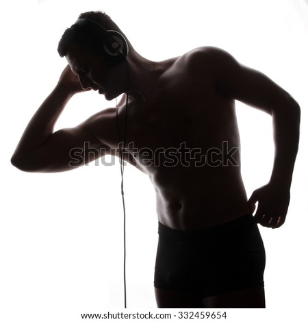 man with headphones listening to music - beautiful male body - athletic torso