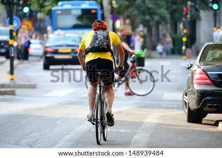 Man with helmet bicycling in traffic - stock photo
