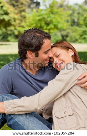 Man with his arm around his friend who is resting her head on his shoulders with her eyes closed - stock photo
