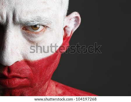 Man with his face painted with the flag of Poland.  The man is serious and photographic composition leaves only half of the face. - stock photo