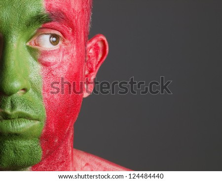 Man with his face painted with the flag of Portugal. The man is looking at side. - stock photo