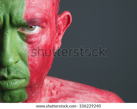 Man with his face painted with the flag of Portugal. The man is serious and photographic composition leaves only half of the face. - stock photo