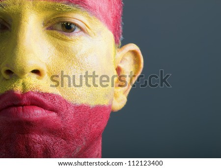 Man with his face painted with the flag of Spain. The man is serious and photographic composition leaves only half of the face. - stock photo