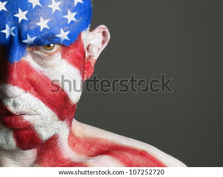 Man with his face painted with the flag of USA. The man is serious and photographic composition leaves only half of the face. - stock photo