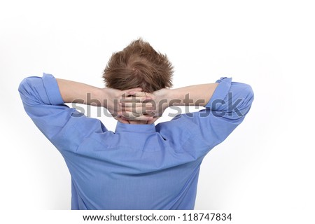 Man with his hands clasped behind his neck - stock photo