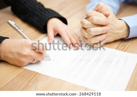Man  with his hands clasped is waiting woman to sign the contract - stock photo