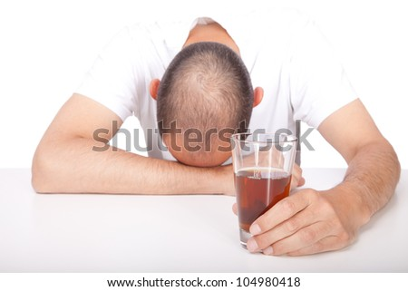 Man with his head on the table holding an alcoholic beverage in his hand - stock photo