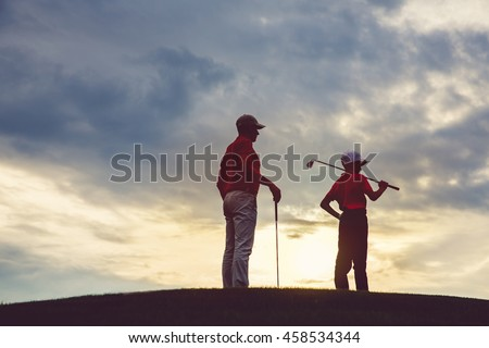 man with his son golfers standing on golf course at sunset, back view - stock photo