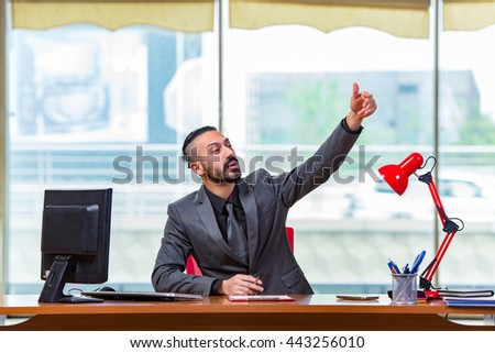Man with his thumbs up in the office desk - stock photo