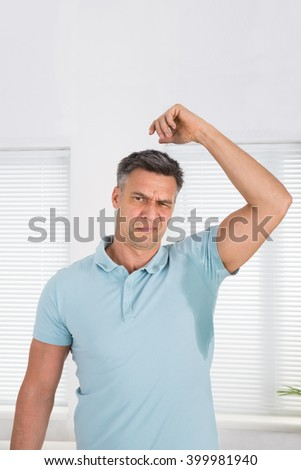 Man With Hyperhidrosis Sweating Very Badly Under Armpit At Home - stock photo