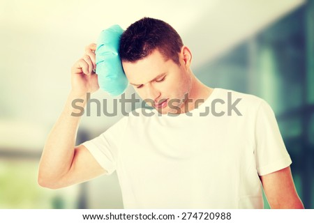 Man with ice bag for headaches. - stock photo