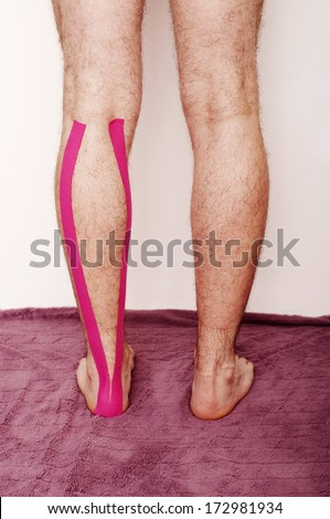 Man with kinesio taping tape on his leg - stock photo