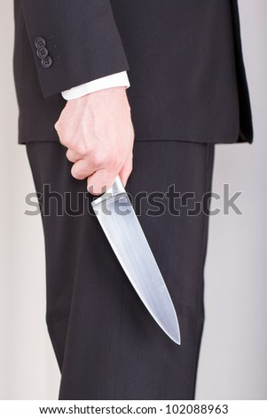 Man with knife, business suit, focus on the knife