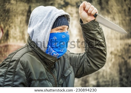 Man with knife near old stone wall - stock photo