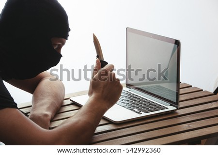 Man with knife sits by the laptop