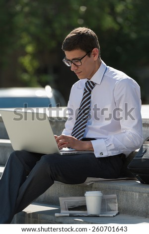 Man with laptop and coffee at summer park on bright day
