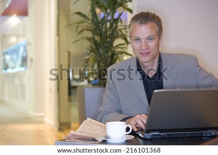 Man with laptop computer by coffee cup, portrait - stock photo