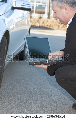 Man with laptop Controls the car - stock photo