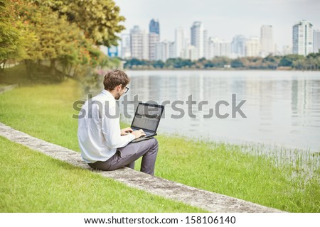 man with laptop in park of megapolice - stock photo
