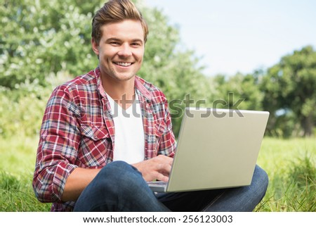 Man with laptop in park on a sunny day