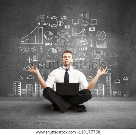 man with laptop meditation and business plan on wall - stock photo