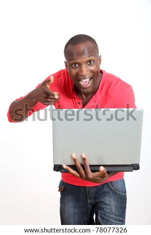 Man with laptop on white background pointing at camera